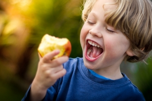cute blonde child about to take a bite of an apple
